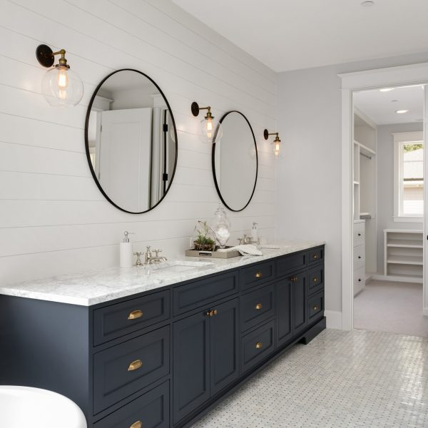 Beautiful-White-and-Bright-Bathroom-in-New-Luxury-Home-with-Large-Vanity-and-Dark-Blue-Cabinets.Features-Bathtub-and-Two-Sinks,-and-Circular-Mirrors